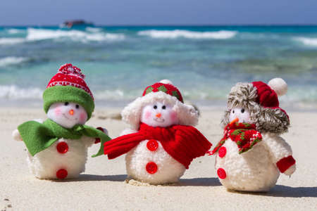 Family of Snowmen in santa hats at tropical beach. New Year's and Christmas holiday in hot countries concept. Stock Photo