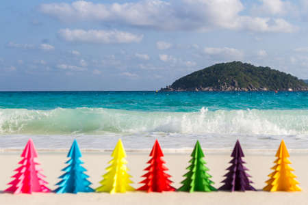 Seven paper Christmas trees stand in the sand against the blue sea. Similan Islands