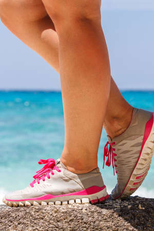 Runner woman stands on a rock near the blue sea. Red laces gray sneakers. Closeup. Photo knee Stock Photo