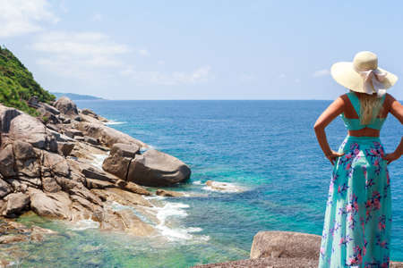 Girl in a blue dress standing on stone and looking into the distance of the horizon Stock Photo