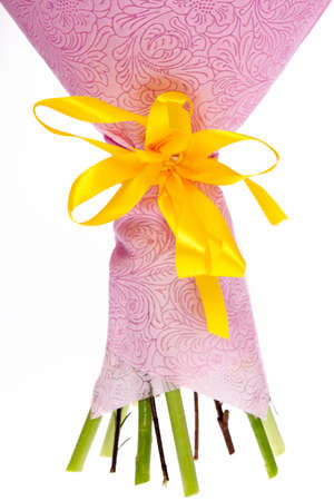 A yellow ribbon on a floral bouquet, white isolated background.