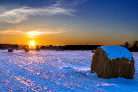 rural field with cut grass, a haystack and the first snow, Russia Stock Photo