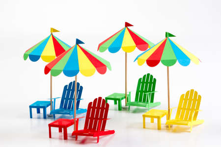 Bright umbrellas folding chairs are made of paper on a white background