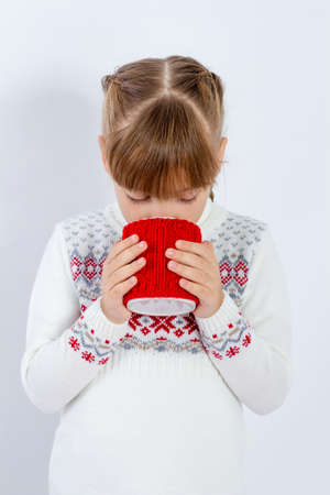 Girl in warm sweater is holding white mug in hands.. Mockup for winter gifts design. Banque d'images