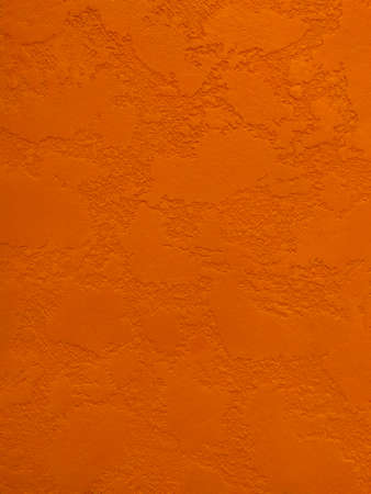 Orange textured wall in decorative plaster, background