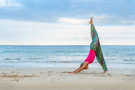 Young attractive woman practicing yoga on the beach. Outdoors yoga. Exercises in nature 写真素材