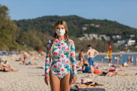 A woman and a child in a protective surgical mask on their face are standing on the beach in swimsuits. coronavirus disease COVID-19 is dangerous.