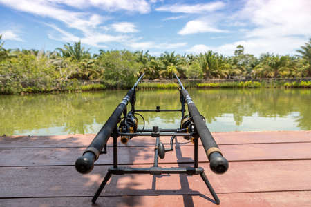 Fishing rod, spinning reel on the background of the lake. Lake for bottom fishing