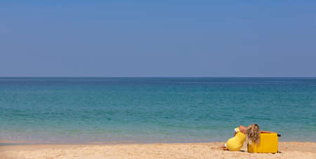 Beautiful girl in a yellow dress on the beach with a yellow suitcase. Blue sea. Yellow sand