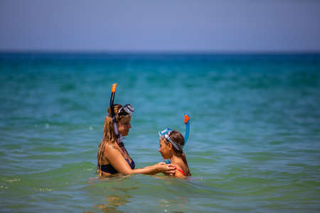 Mom with a daughter in masks for snorkeling