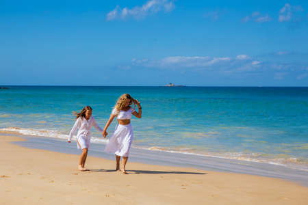 Young beautiful mother with her charming daughter in white clothes walk on a sandy beach near the water