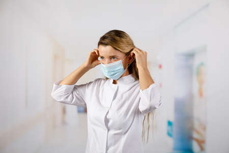 The doctor puts on a protective mask against viral infection. Protection from COVID-19