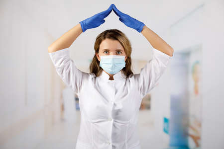 A masked female doctor holds her hands above her head. Banque d'images - 149800829