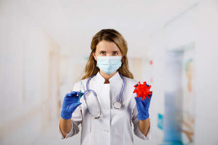 A masked female doctor holds a model 2019-nCoV (SARS-CoV-2).