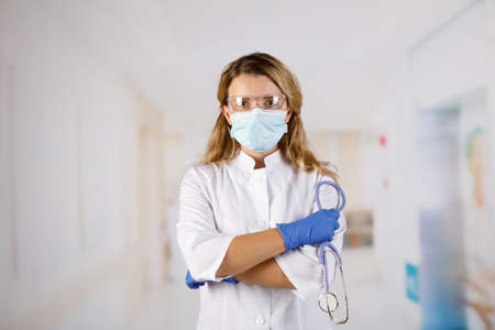 Confident woman doctor wearing medical mask standing with crossed arms. female portrait.