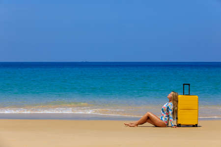 Beautiful girl in a swimsuit on the beach with a yellow suitcase. Blue sea. Yellow sand Banque d'images