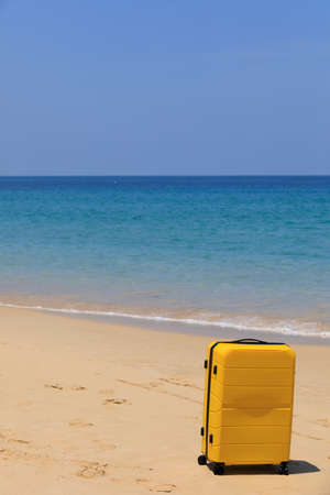 Yellow tourist suitcase on the beach near the blue water.