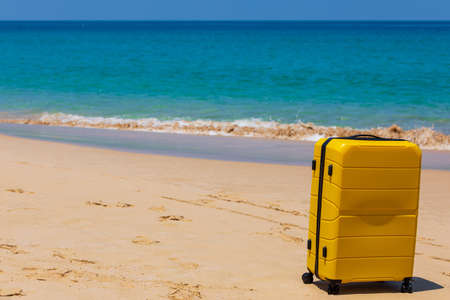 Yellow tourist suitcase on the beach near the blue water. Banque d'images - 151695332
