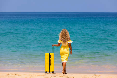 Beautiful girl in a swimsuit on the beach with a yellow suitcase. Blue sea. Yellow sand Banque d'images - 151695035