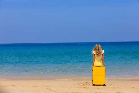 Beautiful girl in a swimsuit on the beach with a yellow suitcase. Blue sea. Yellow sand Banque d'images - 151695298