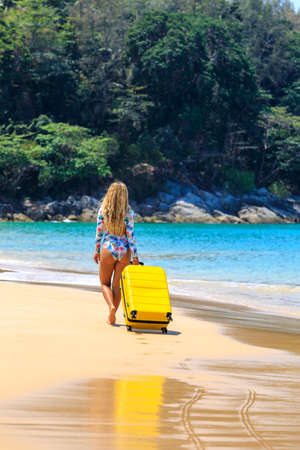Beautiful girl in a swimsuit on the beach with a yellow suitcase. Blue sea. Yellow sand Banque d'images - 151694942