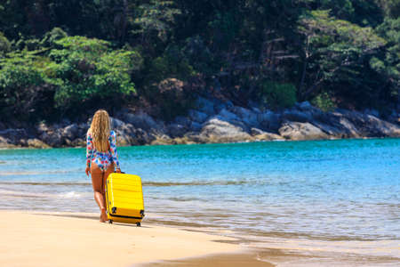 Beautiful girl in a swimsuit on the beach with a yellow suitcase. Blue sea. Yellow sand Banque d'images - 151695073