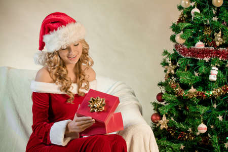 Portrait of a smiling woman holding Christmas giftin front of Christmas tree photo
