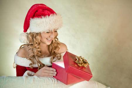 Portrait of a beautiful woman in santa hat lookingat Christmas present Stock Photo - 12178335