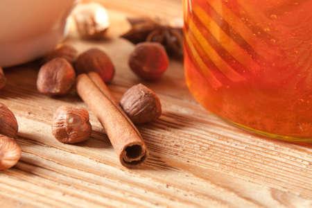 Close-up of a cinnamon stick next to a honey jar