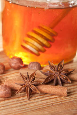 Anise stars and cinnamon sticks left in front of a honey jar with honey spoon in it.