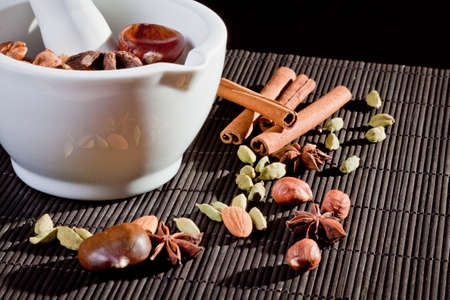 Nuts and cinnamon sticks in front of a mortar Stock Photo