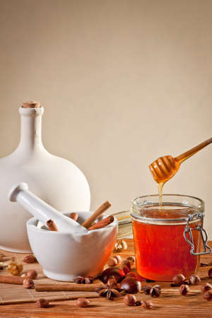 Honey dripping into a jar next to a mortar filled with cinnamon sticks Stock Photo