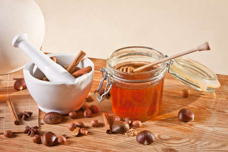 Honey jar next to a mortar filled with cinnamon sticks Stock Photo - 12582798