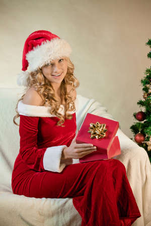 Young woman in santa hat with a gift