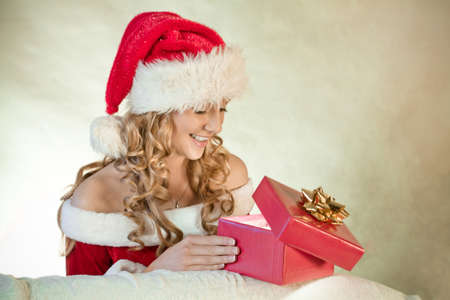 Portrait of a young woman in santa hat looking at Christmas present