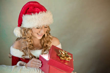 Portrait of a beautiful woman in santa hat smiling at Christmas present