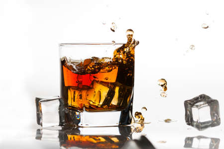 Whiskey on the rocks splashed by ice cubes