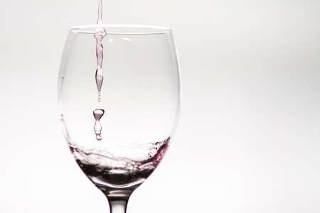 Drop of wine falling into a wineglass
