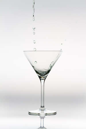 Drops of liquor falling into a cocktail glass Stock Photo