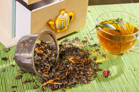 Dried tea next to a cup Stock Photo