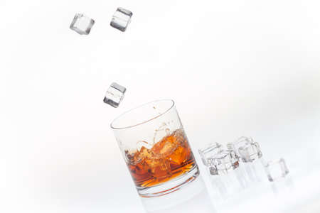 Whiskey on the rocks splashed by falling ice cubes