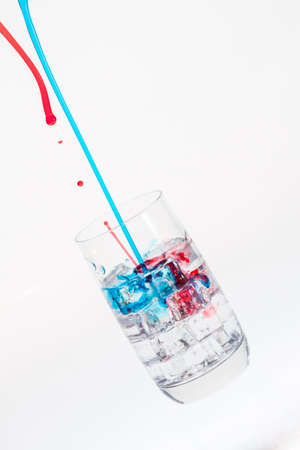 Colorful droplets falling into a drink