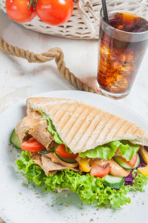 Kebab in grilled pita bread next to cold beverage Stock Photo