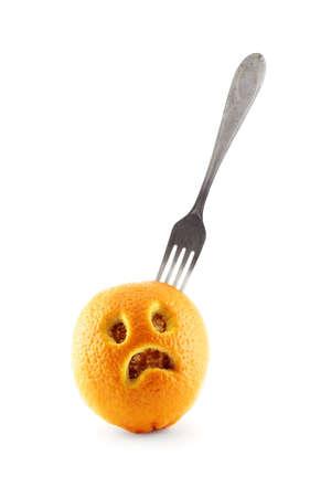 Fork put into an orange with sad face