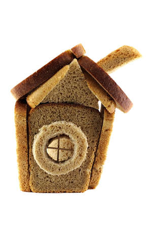 dwell: House made of rye-bread loafs over white background