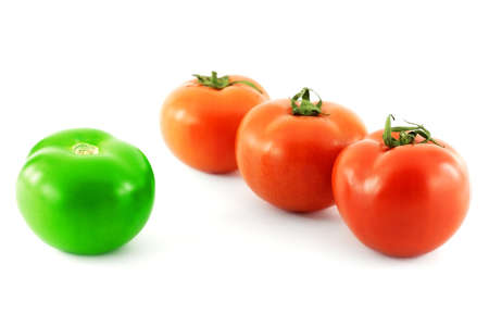 Three red tomatoes standing against a green one Stock Photo