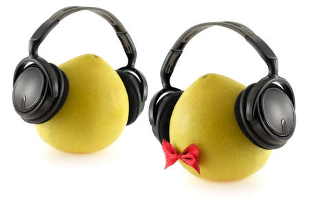Two pomelo fruits with headphones over white background Stock Photo
