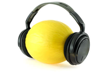 Melon with headphones over white background