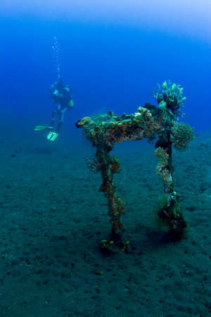 indo: Diver with part of the liberty wreck over volcanic black sand. Taken at Tulumben, Bali, Indonesia.