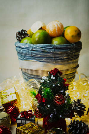 Christmas Festive Decoration Set With a Small Christmas Tree and Green Tangerines. Still Life